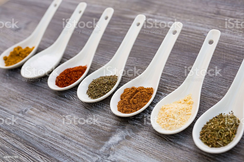 eight ceramic spoons with spices stock photo