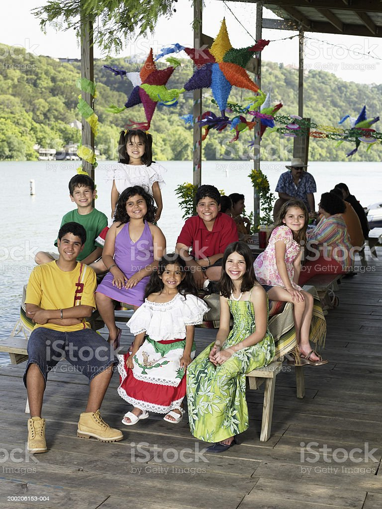 Eight children (4-12) sitting at picnic table, smiling, portrait royalty-free stock photo