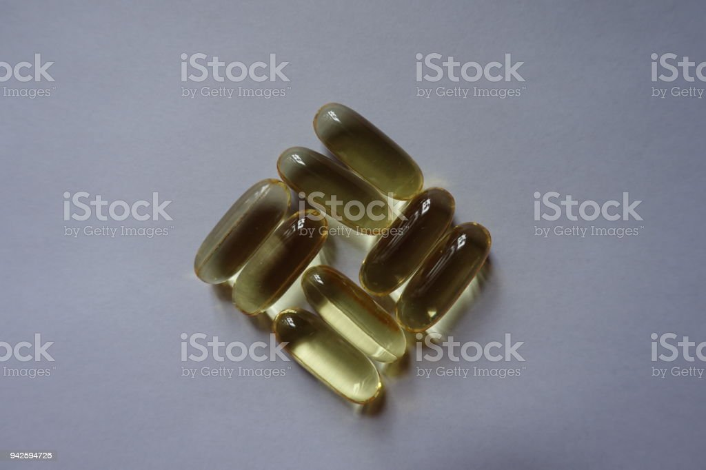 Eight fish oil capsules in a shape of basketweave pattern stock photo