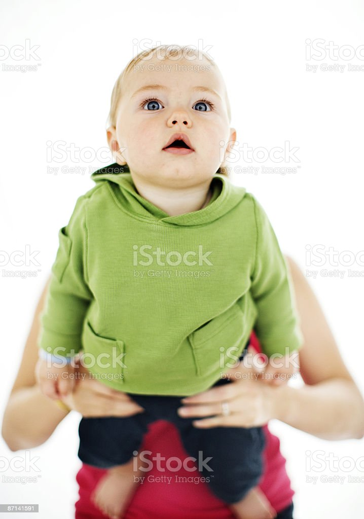 Eight month old baby boy in mother's arms photo libre de droits