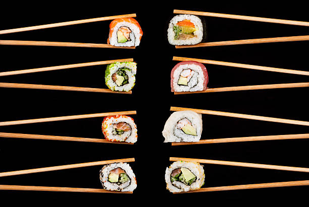 Eight pairs of chopsticks holding pieces of Sushi rolls stock photo