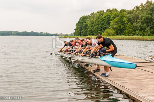 Trakai, Lithuania - July 26, 2013: Eight people holding an eight that is a rowing boat used in the sport of competitive rowing. This summer touristic attraction is very popular in Trakai, Lithuania