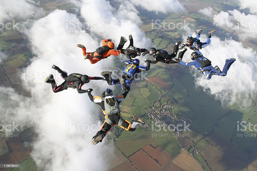 Eight skydivers in free fall through clouds stock photo