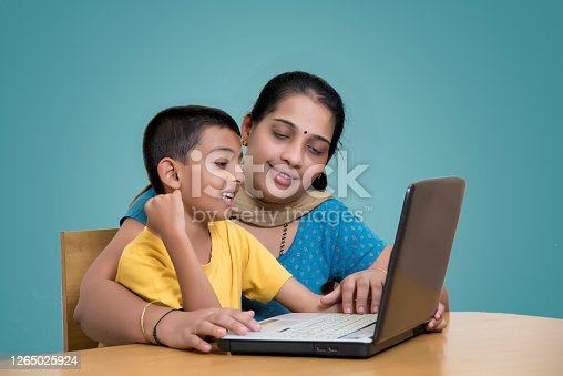 eight year old Indian boy attending online class with laptop  at home and his mother helping him