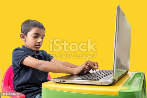 eight year old Indian boy attending online class at home