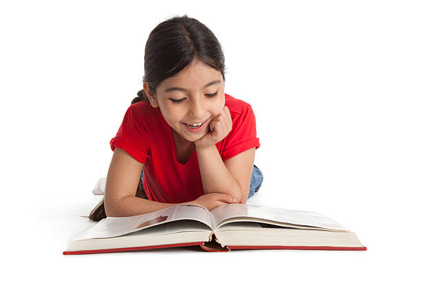 Eight year old girl smiling while reading a book stock photo