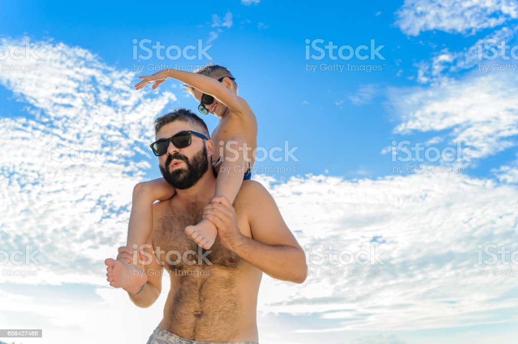 Eight years old boy sitting on dad's shoulders. Both in swimming shorts and sunglasses, having fun on the beach. Bottom view. Blue sky and altocumulus clouds behind them stock photo