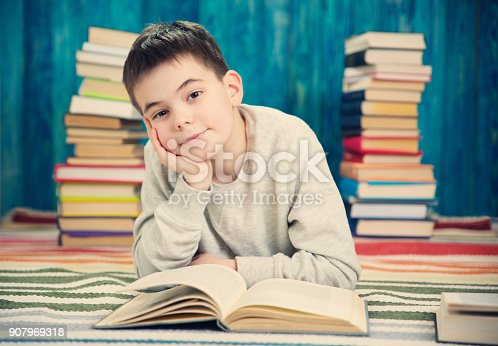 683105722 istock photo eight years old child reading a book 907969318