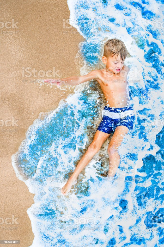 Eight years old handsome blond boy lying on the sand, eyes shut, attracted waves rolls and cover him as if coverlet. View from above. Vibrant colors concept stock photo