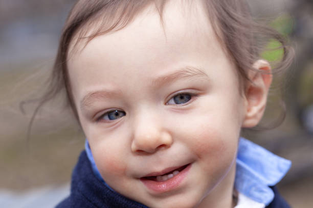 Eighteen month blue-eyed baby boy outdoors looking away stock photo