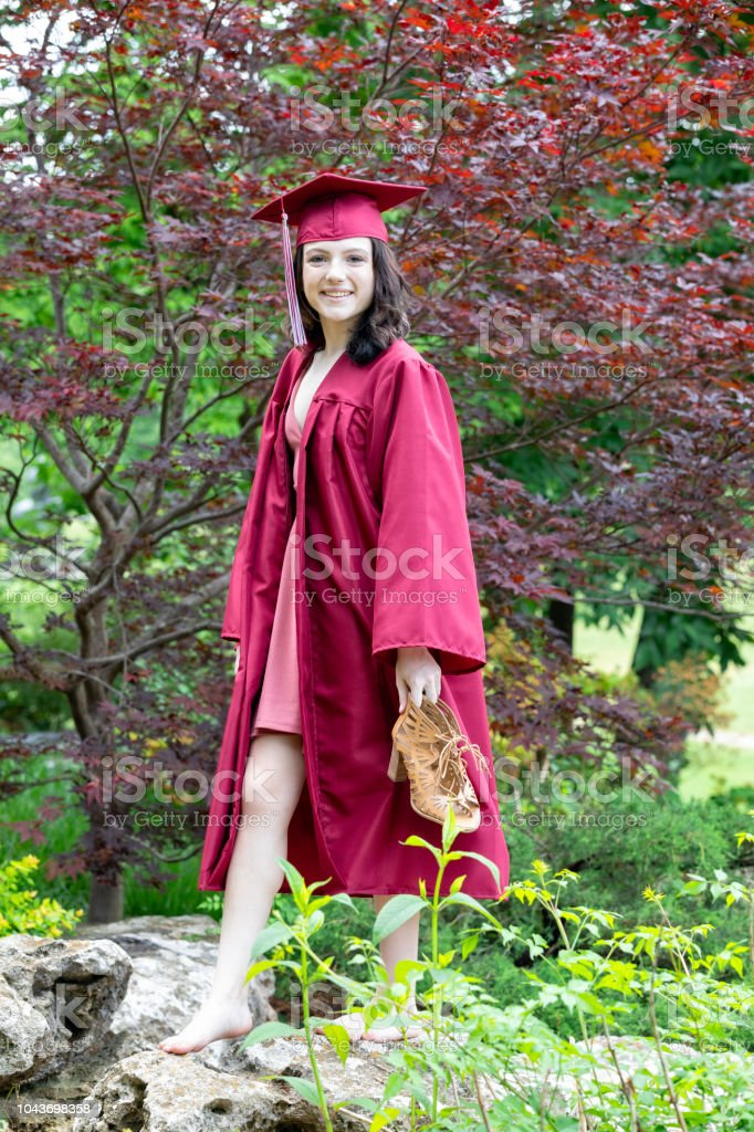 Eighteen Year Old Woman Enjoys a Walk in the Park after Graduation stock photo