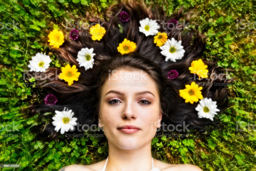 Eighteen Year Old Woman lying down with flowers throughout her hair stock photo
