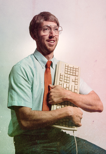 A nerd computer tech guy poses for a glamour portrait hugging his computer keyboard with love.  Vintage 1980's emulation and style of the portrait and the clothing and technology.  A funny and humorous depiction of the digital technology of decades past.