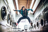 A man in late 1980's youth style does his laundry at an old school laundromat, dancing while listening to music on a walkman personal stereo and a colorful sweater in the walkway between the washers and dryers while waiting for his clothing to finish drying.  Horizontal image.