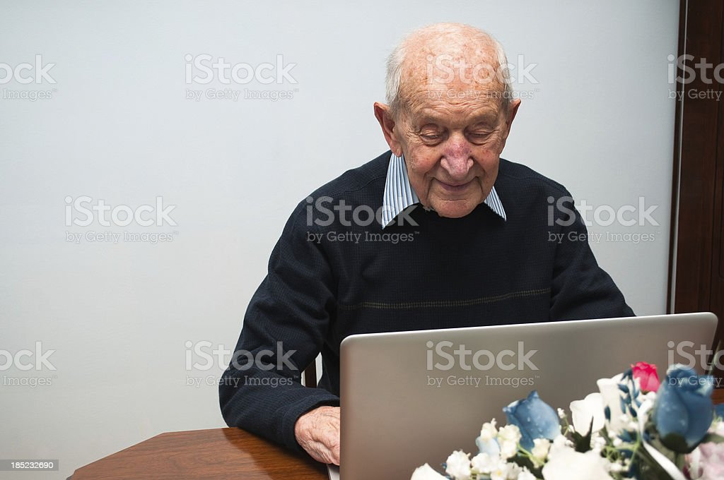 Eighty nine year old senior man using portable computer stock photo