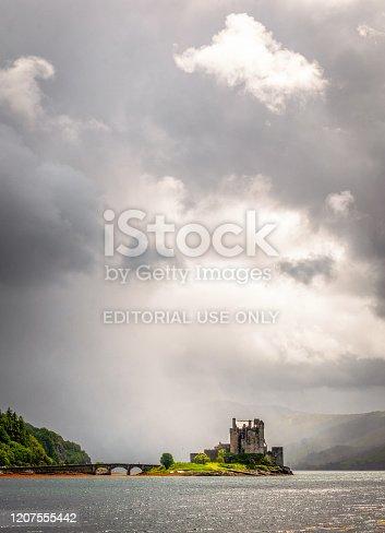 Eilean Donan Castle, Scotland - Seen across the water of Loch Duich, Eilean Donan in wet weather, below a stormy grey sky.