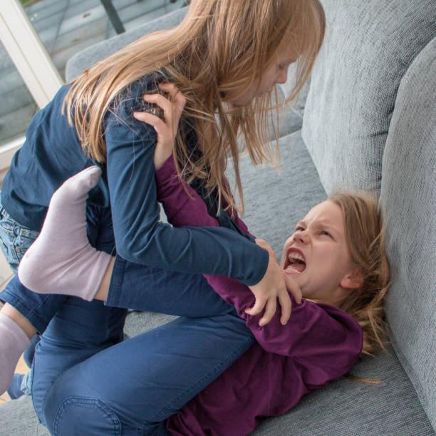 Ein 7- und ein 9-jähriges Mädchen schreien sich an und schlagen sich Ein 7- und ein 9-jähriges Mädchen schreien sich an und schlagen sich sibling stock pictures, royalty-free photos & images