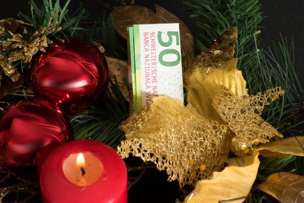ein adventskranz, weihnachten und 50 schweizer franken geldschein - weihnachten stok fotoğraflar ve resimler