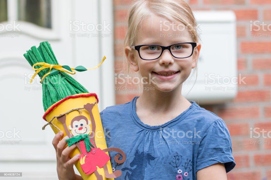 Ein blondes Mädchen hält seine Schultüte und lächelt in die Kamera stock photo