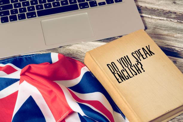 Computadora de Ein, Flagge von Großbritannien und Buch mit dem Titel Sprechen Sie englisch - foto de stock