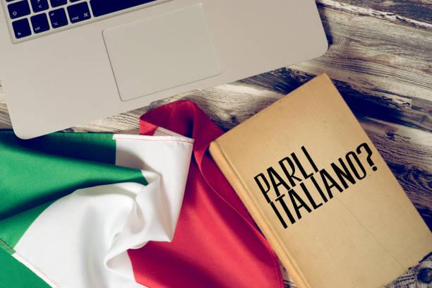 Ein Computer, Flagge von Italien und Buch mit dem Titel Sprechen Sie italienisch stock photo