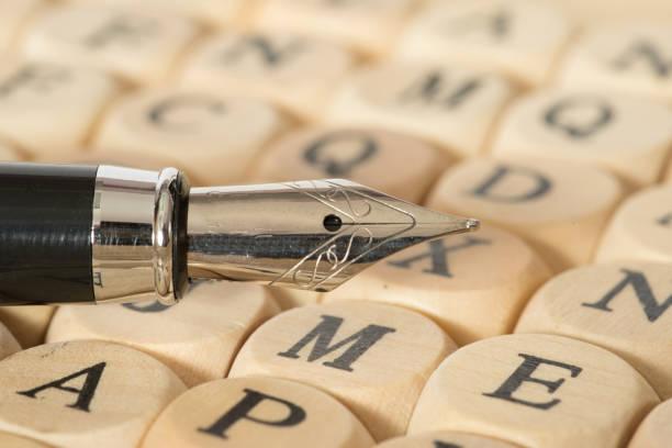 Ein Füllfederhalter und verschiedene Holzbuchstaben Ein Füllfederhalter und verschiedene Holzbuchstaben illiteracy stock pictures, royalty-free photos & images