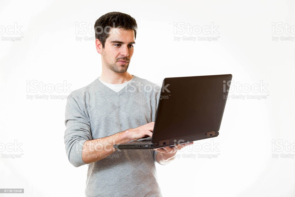 Ein Junger Mann arbeitet im Stehen an einem Laptop stock photo