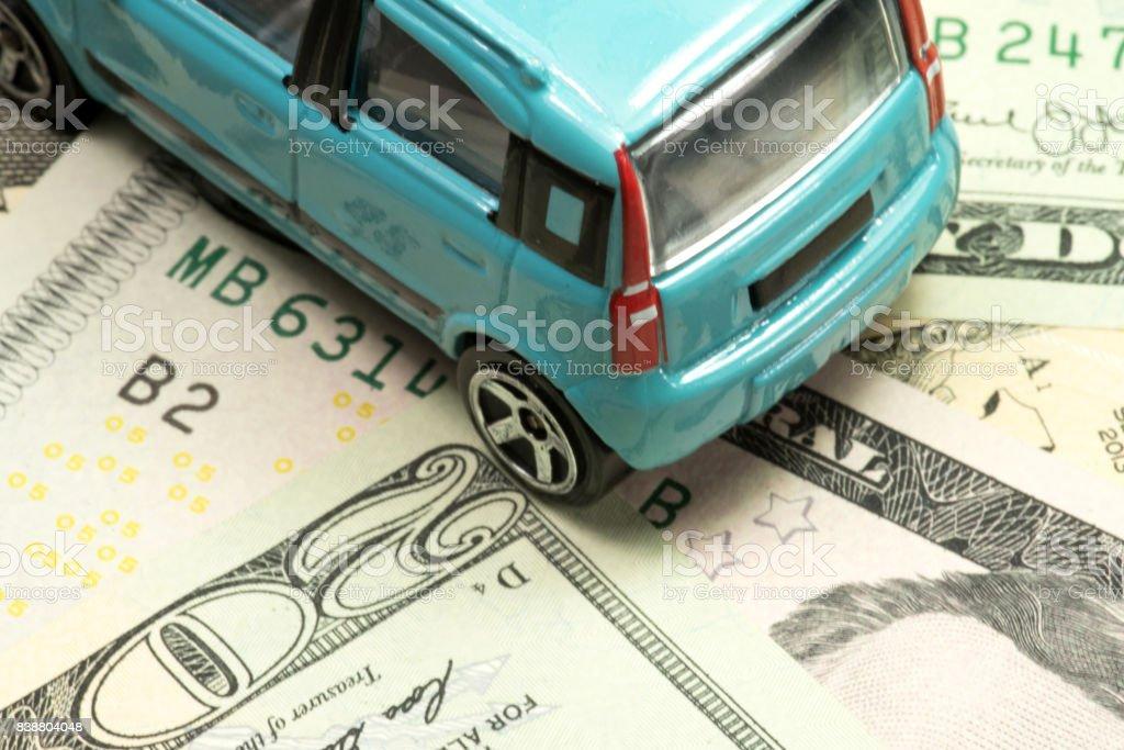 Ein Kleinwagen und Geldscheine Dollar - Photo