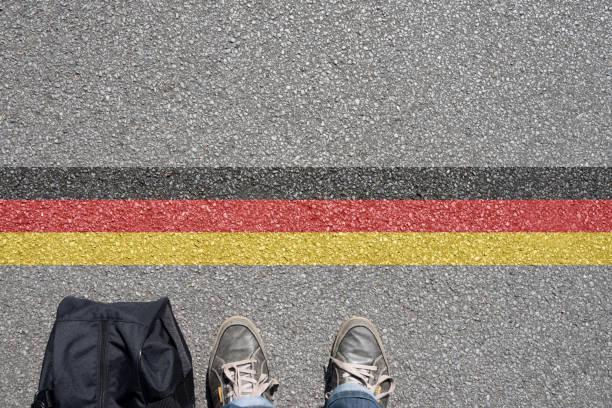 ein mann mit einem koffer steht un der grenze zu deutschland - alemania fotografías e imágenes de stock