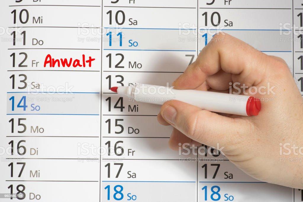 Ein Mann vermerkt einen Termin beim Anwalt in einem Kalender stock photo