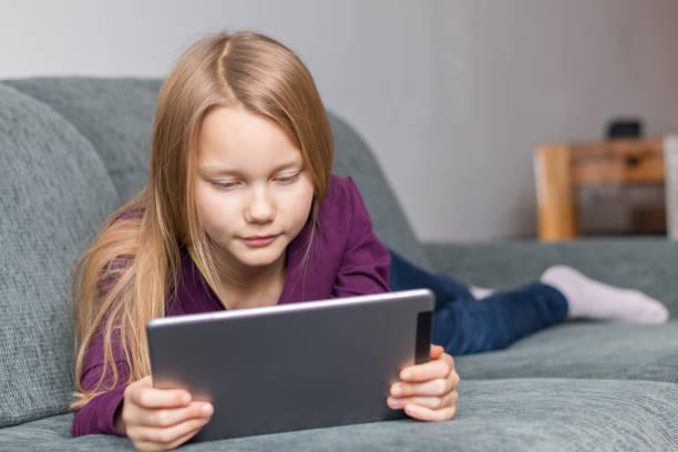 ein mädchen liegt mit einem tablet-pc im wohnzimmer auf dem sofa - lila mädchen zimmer stock-fotos und bilder