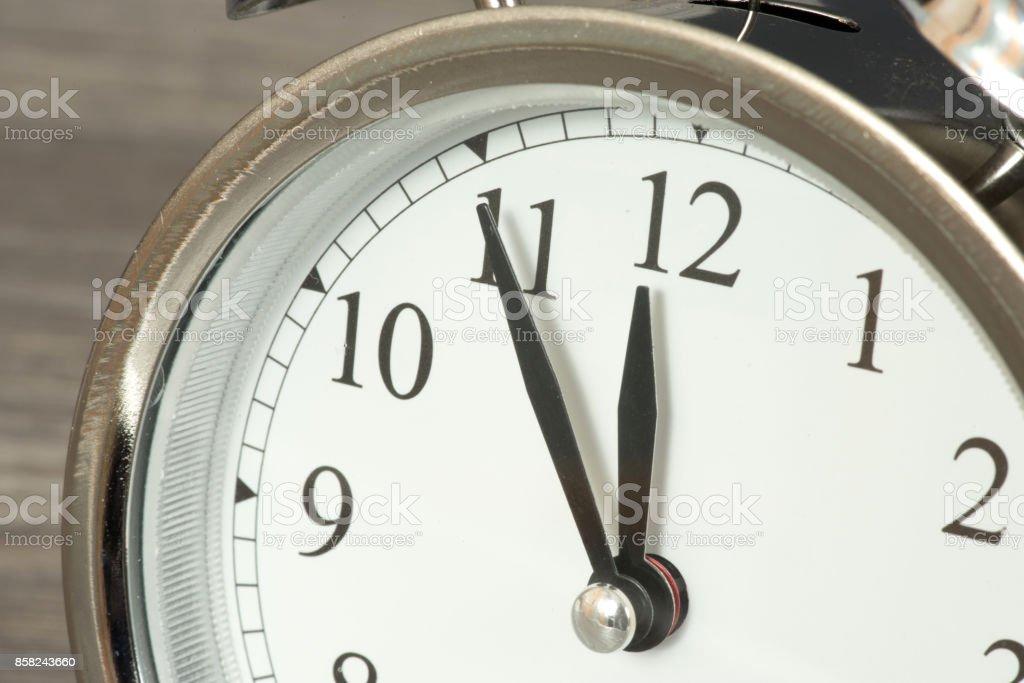 Ein Wecker steht auf fünf vor zwölf Uhr stock photo