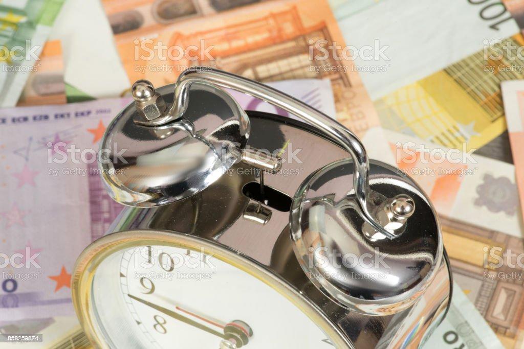 Ein Wecker und viele Euro Geldscheine stock photo