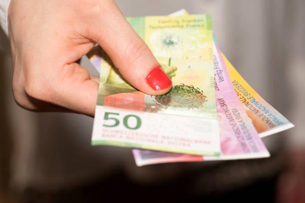 eine frau hält schweizer franken bankbiljettendrukkerij in der hand - franken stockfoto's en -beelden