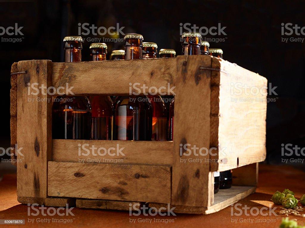 Eine Holzkiste mit Bierflaschen und frischem Hopfen auf rostiger Platte stock photo