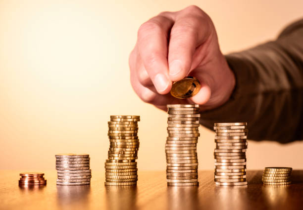 Eine Münze wird auf einen Stapel mit Münzen gelegt Mehrere Stapel mit Münzen. Auf einen Stapel wird eine weitere Münze gelegt. monetary policy stock pictures, royalty-free photos & images