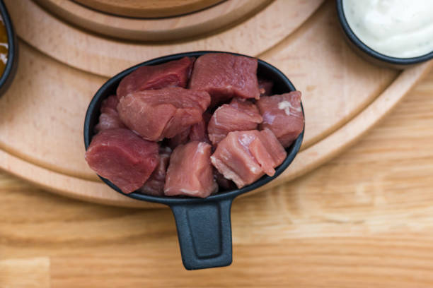 eine schüssel schweinefleisch in stücke auf einer gemeindereise platte, sterben zum fondue bereit ist - schweinegulasch stock-fotos und bilder