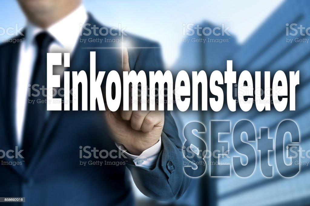Einkommensteuer (in german Income tax) touchscreen is operated by businessman. stock photo
