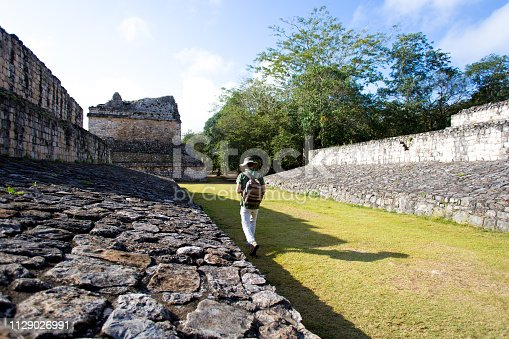Ek'Balam, Yucatan, Mexico: A senior male tourist with a sunhat and backpack explores ball court at the Mayan archaeological zone of Ek'Balam, just north of  Valladolid in the Yucatan Peninsula, Mexico.