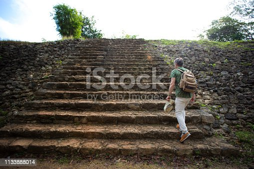 Ek'Balam, Yucatan, Mexico: A senior male tourist with a backpack approaches the Mayan archaeological zone of Ek'Balam, just north of  Valladolid in the Yucatan Peninsula, Mexico.
