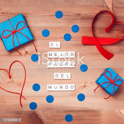 Feliz dia del padre words made of wooden blocks with blue gift boxes and red hearts on wooden background. Happy fathers day greeting card, holiday flat lay