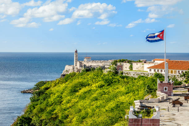 el morro spanish fortress with lighthouse, cannons and cuban flag in th foreground, with sea in the background, havana, cuba - cuba stock photos and pictures