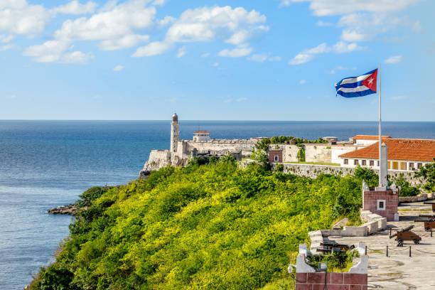 Spanische Festung El Morro mit Leuchtturm, Kanonen und kubanische Flagge in th Vordergrund mit Meer im Hintergrund, Havanna, Kuba – Foto