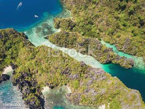 Aerial view down to the famous Big Lagoon Sea Channel at Miniloc Island with typical filipino Balangay Boats and Kayaks. Aerial Drone Point of View. Miniloc Island, Mimaropa, El Nido, Palawan, Philippines, Southeast Asia, Asia