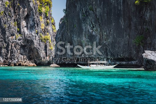 istock El Nido, Palawan, Philippines. Rock formation and tourism boat in ocean lagoon near entrance to secret lagoon beach. 1227203358