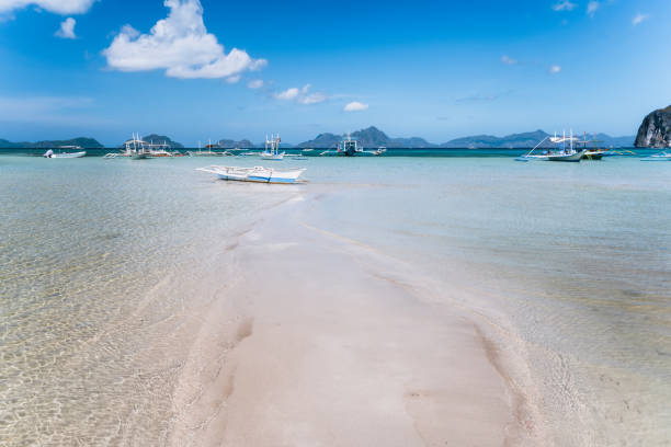 El Nido, Palawan, Philippines. Tropical scenery of banca boat on the sandy beach in low tide El Nido, Palawan, Philippines. Tropical scenery of banca boat on the sandy beach in low tide. pinagbuyutan island stock pictures, royalty-free photos & images