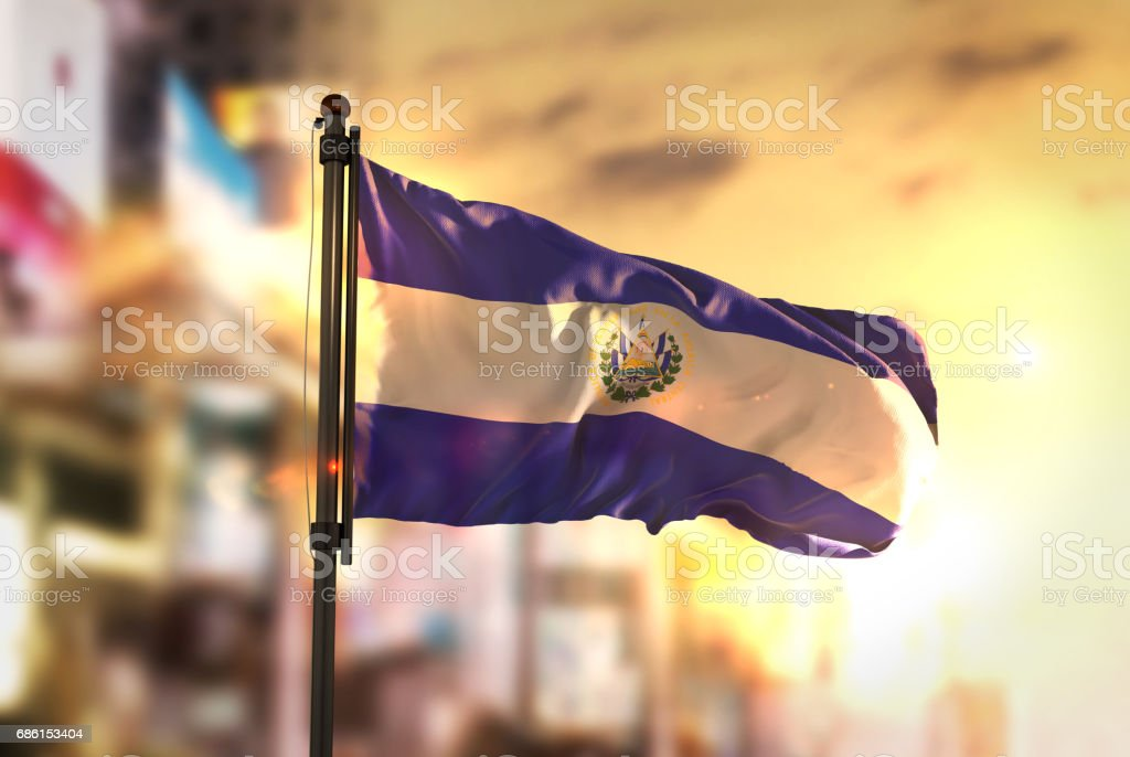Bandera del Salvador contra la ciudad borrosa de fondo en contraluz amanecer - foto de stock