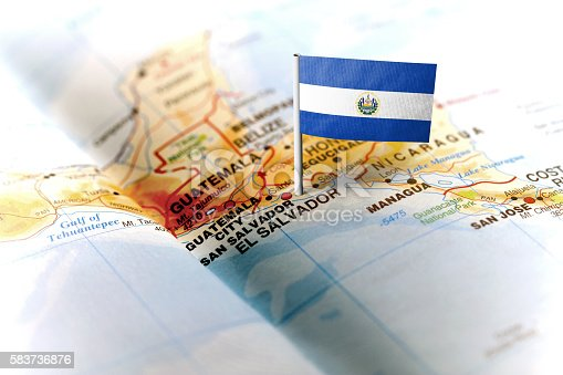 The flag of El Salvador pinned on the map. Horizontal orientation. Macro photography.