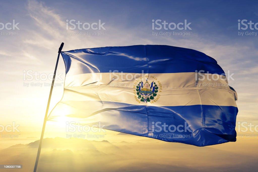 El Salvador salvadoreño bandera tela de paño que agita en la niebla de la niebla de amanecer superior - foto de stock