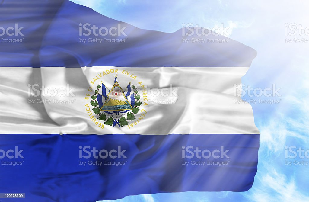 El Salvador waving flag against blue sky with sunrays royalty-free stock photo
